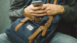 muž s batohem na klíně kouká do telefonu