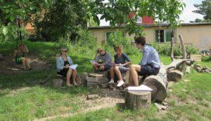 pět lidí sedí na lavičkách v zahradě
