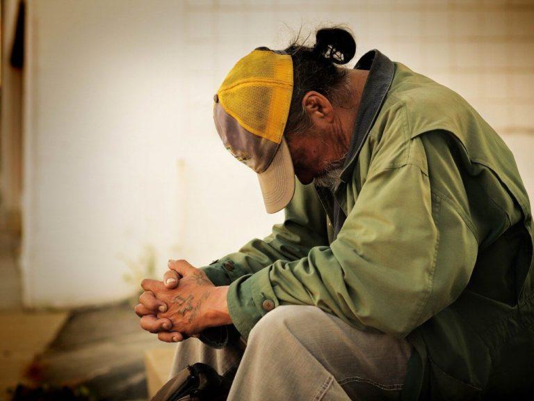 muž bez domova sedí se svěšenou hlavou