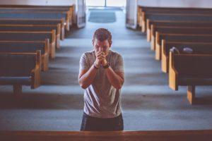mladý muž modlící se v kostele