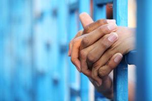 mužské ruce prostrčené skrze mříže
