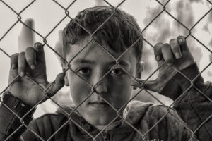 smutný chlapec za plotem
